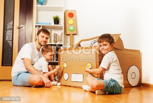 496487362 istock photo Kids painting headlights on toy cardboard car 530579750