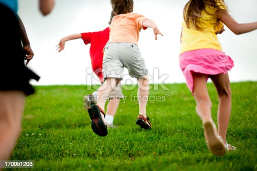 A group of diverse children playing outside. Extremely shallow focus and slight motion blur.