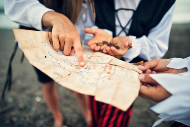 kids pirates reading treasure map on a beach - pirates stock photos and pictures