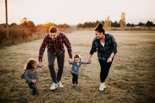 Kids plaing in meadow with parents stock photo