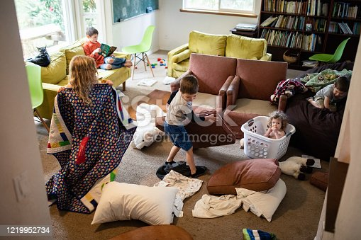 Toys, blankets, and disarranged furniture clutter a living room as kids play at home.  Normal routine or part of social distancing at home.