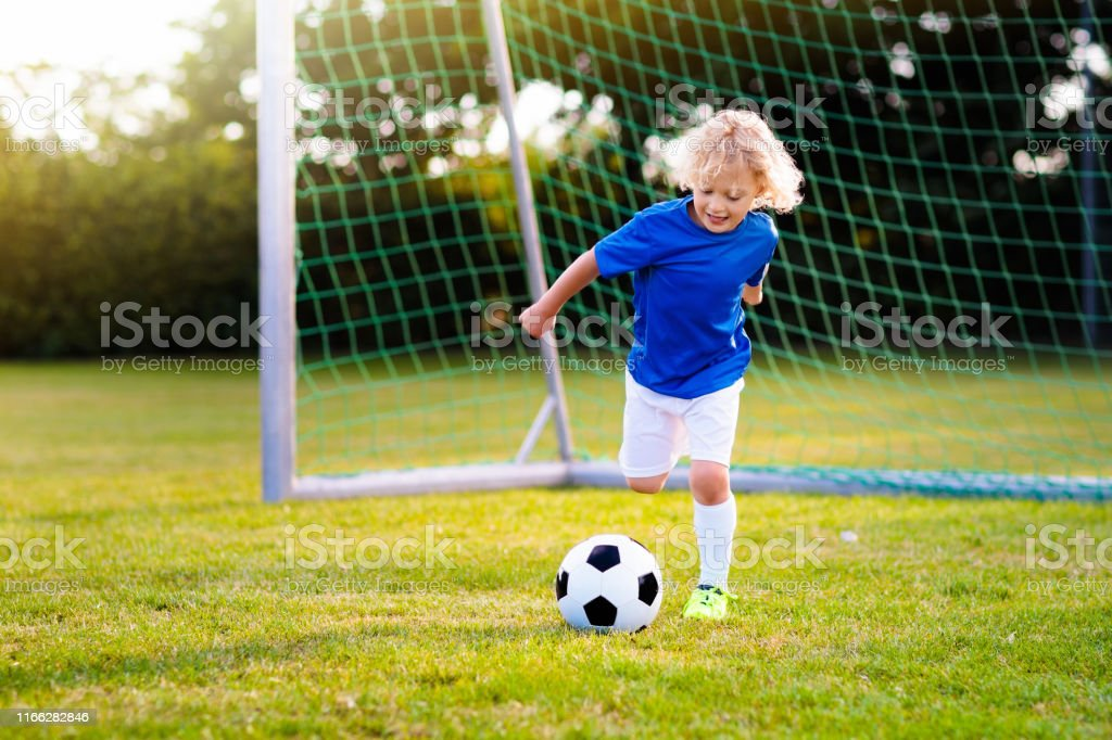 Kids play football on outdoor field. Children score a goal during...
