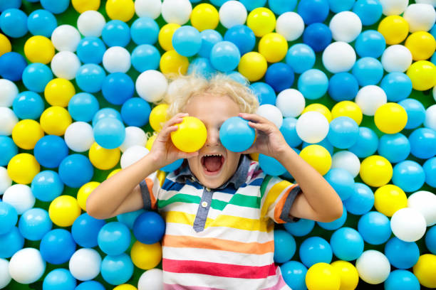 kids play in ball pit. child playing in balls pool - playpen stock pictures, royalty-free photos & images