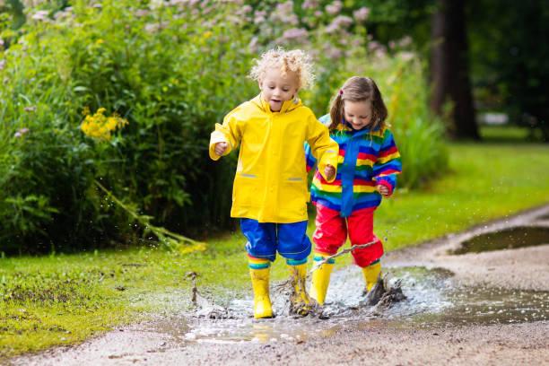 kinder spielen im regen und pfütze im herbst - mädchen dusche stock-fotos und bilder