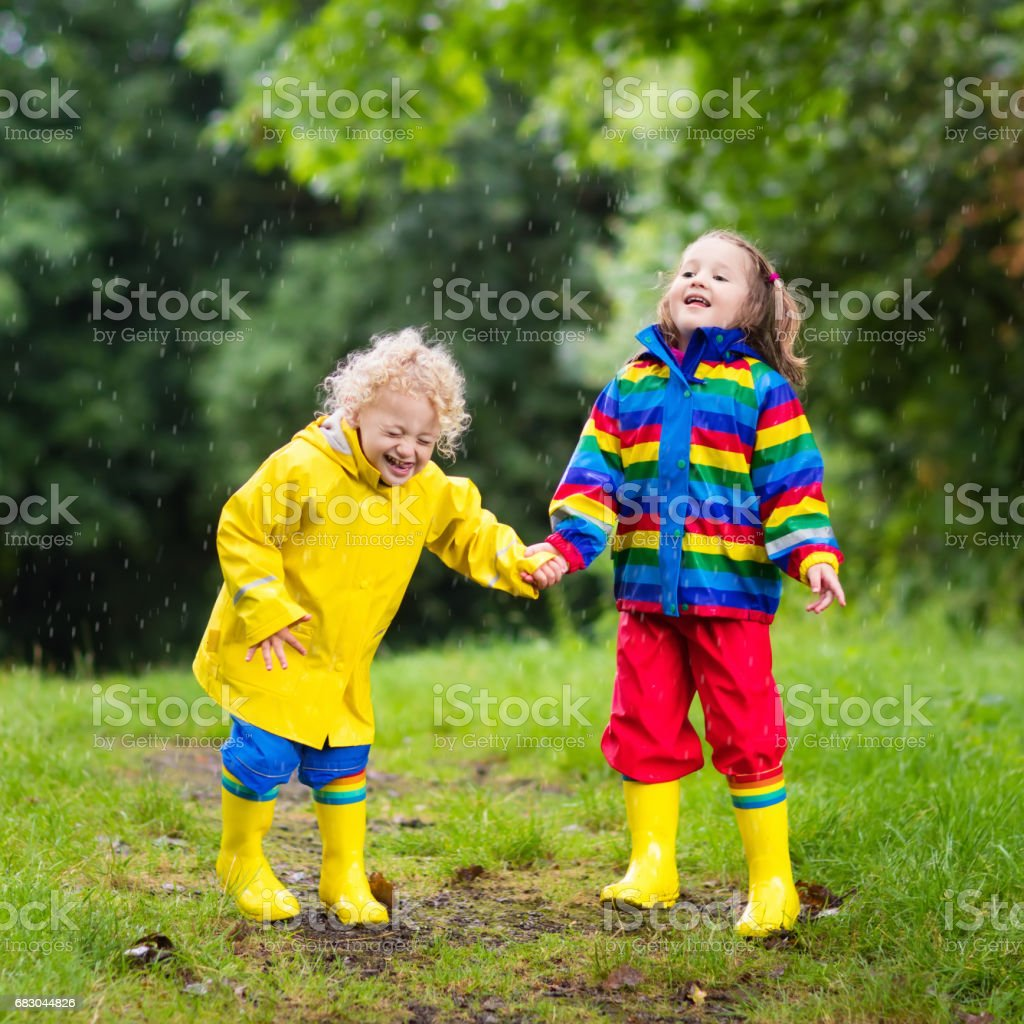 Kids play in rain and puddle in autumn royalty-free stock photo