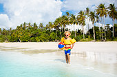 Child playing on tropical beach with palm trees. Little boy with inflatable ball and swim float at sea shore. Family summer vacation. Swimming aid for toddler. Kids play with water and sand toys.