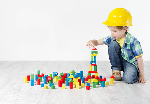 kids play room, child hard hat playing building blocks toys - construction workwear floor bildbanksfoton och bilder