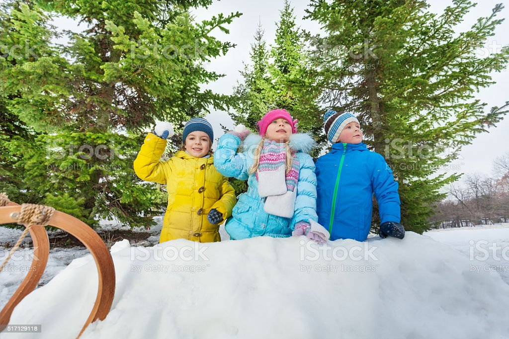 Kids play snowball inside snow fortress in park stock photo
