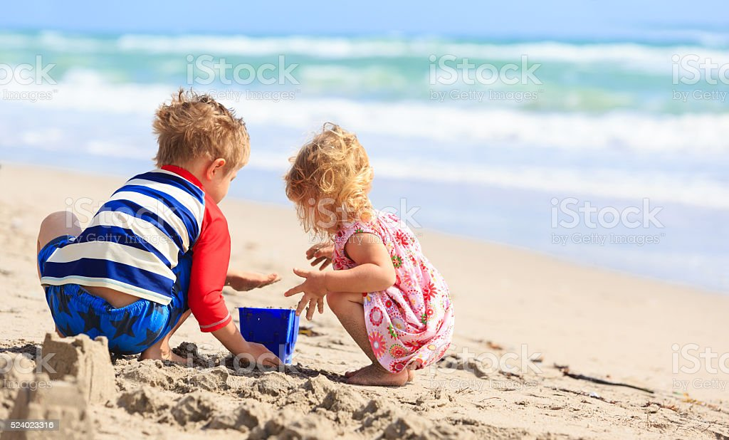 kids play with sand on summer beach stock photo