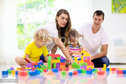 648139780 istock photo Kids play with toy blocks. Family at home. 1212710121