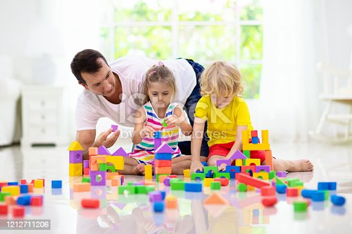 648139780 istock photo Kids play with toy blocks. Family at home. 1212711206