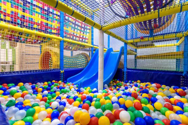 kinderspeelplaats binnen. panoramisch uitzicht in het droge zwembad met kleurrijke ballen en glijbaan. mooie kunststof gym voor activiteit in de speelkamer. - mini amusementpark stockfoto's en -beelden