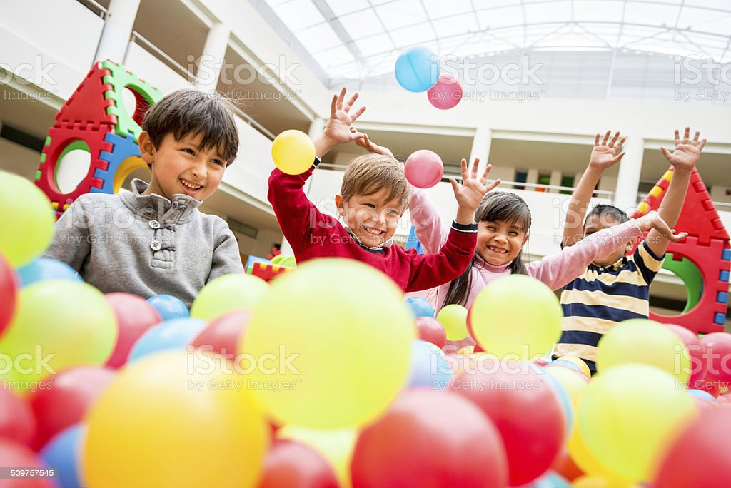 Kids playing at a ball pool stock photo