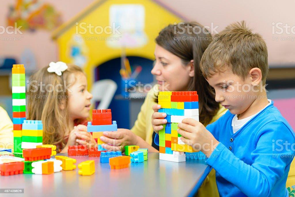Kids Playing at Kindergarten Kids playing with plastic building blocks at kindergarten 2015 Stock Photo