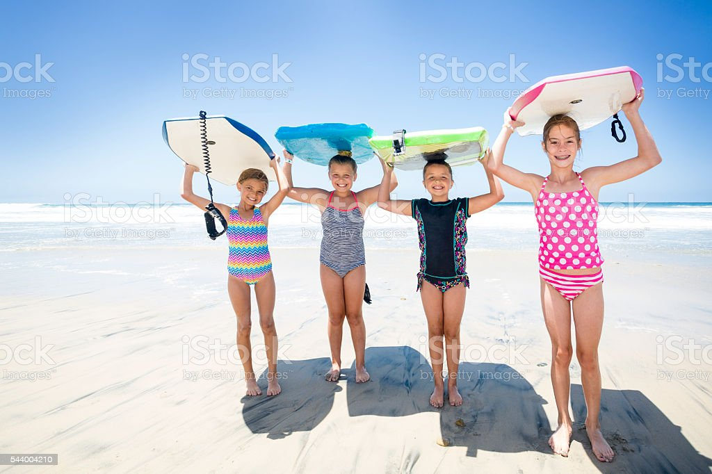 Kids playing at the beach together while on vacation stock photo