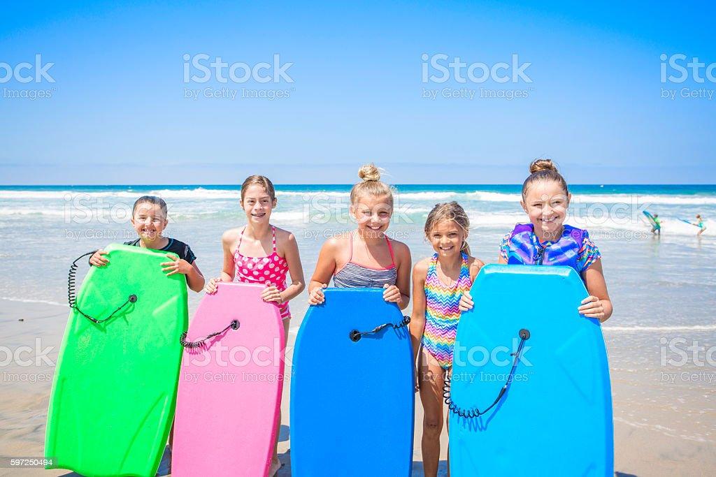 Crianças brincando na praia juntos enquanto de férias - foto de acervo