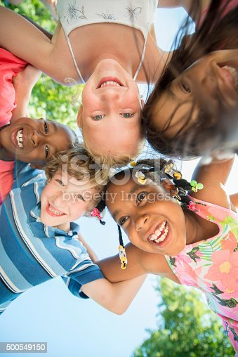 A multi-ethnic group of elementary age children in a huddle and are smiling while looking down at the camera.