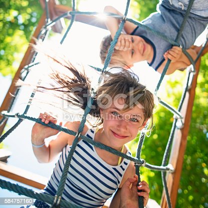Portrait of little girl climbing in the playground. The girl aged 10 is smiling at the camera and her brother aged 6 is smiling in the background. Sunny summer day. Shot from directly below the kids.