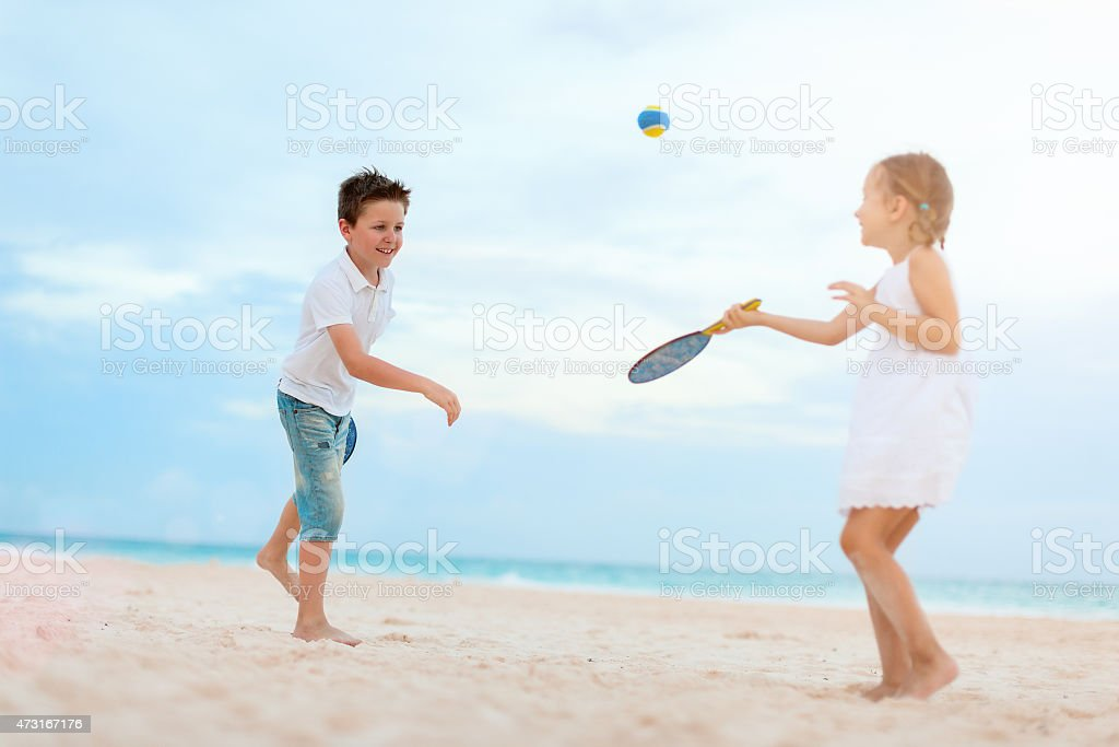 Bambini che giocano sulla spiaggia di tennis - foto stock
