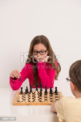 10 years old girl playing with her friend brother chess, making a move.