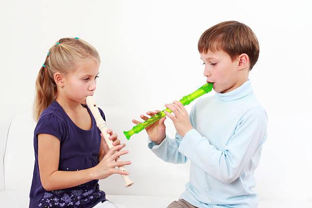 kinder spielen flöte - lautbildungsspiele stock-fotos und bilder