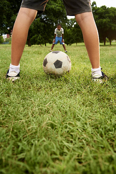 Kids playing football and soccer game in park stock photo