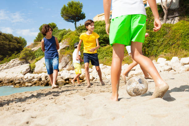 crianças jogando futebol com os pés descalços na areia da praia - futebol de areia - fotografias e filmes do acervo