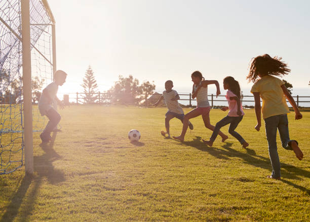Kids playing football in a park, one in goal, side view stock photo
