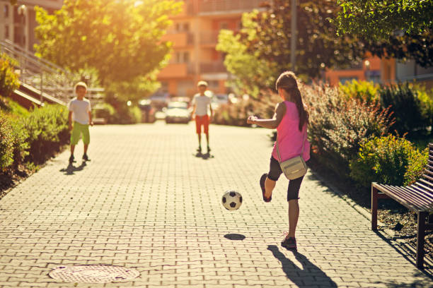 Kids playing football in residential area stock photo