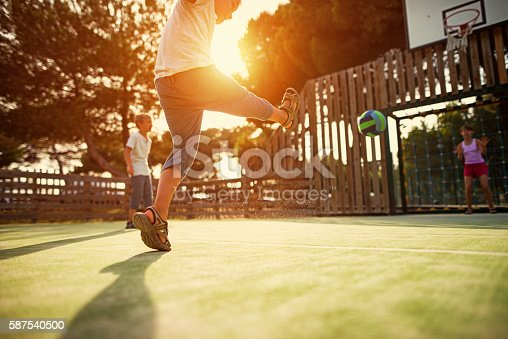 621475196 istock photo Kids playing football in the schoolyard 587540500
