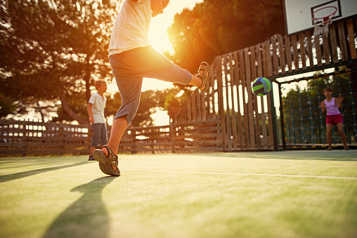 istock Kids playing football in the schoolyard 587540500