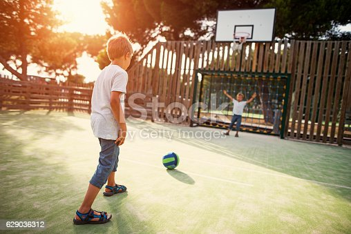 istock Kids playing football in the schoolyard 629036312