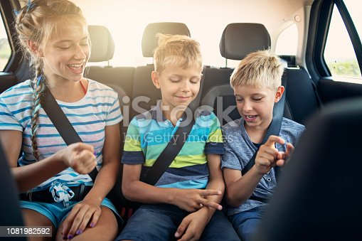 istock Kids playing games in car during road trip 1081982592