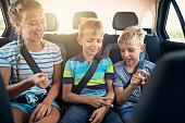 Three kids playing rock paper scissors in car on a road trip. Kids are aged 12 and 9. The kids are laughing and having fun. Sunny summer day.\nNikon D850.