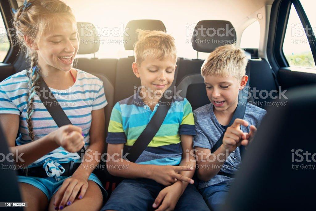 Kinder spielen im Auto während der Fahrt – Foto