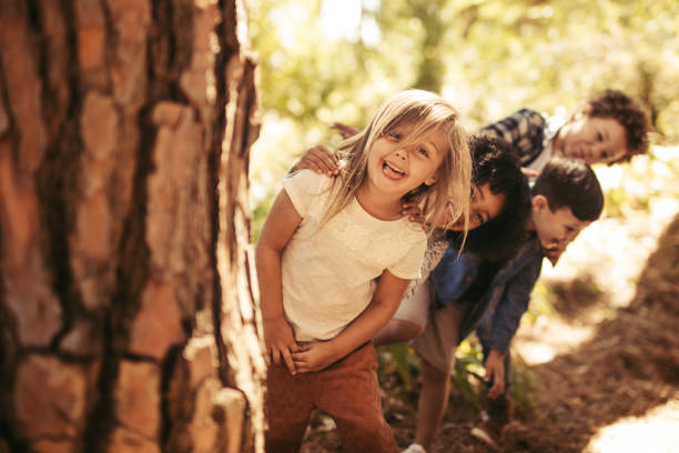 Kids playing hide and seek in a park stock photo