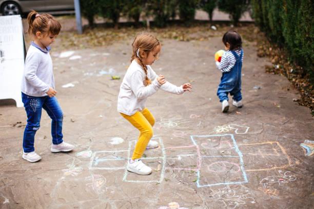 kinder spielen von himmel und hölle auf spielplatz im freien - himmel und hölle spiel stock-fotos und bilder