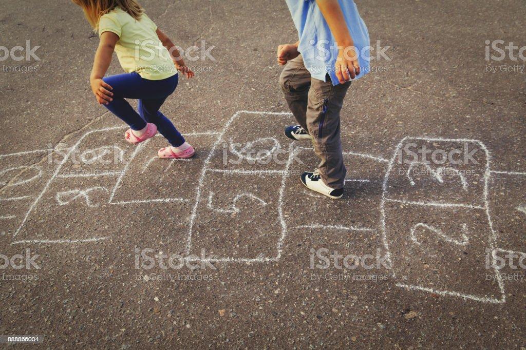 石けり遊びを遊び場で遊ぶ子供たち ストックフォト