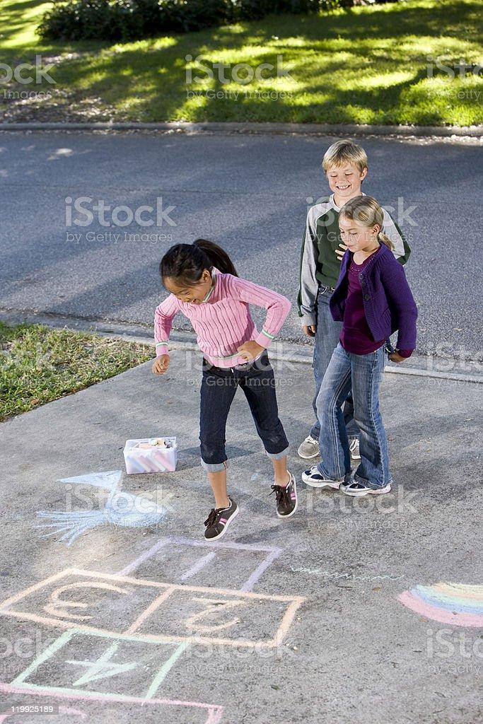 Kids playing hopscotch stock photo
