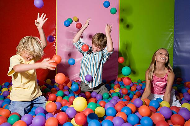 Kids playing in ball pool stock photo
