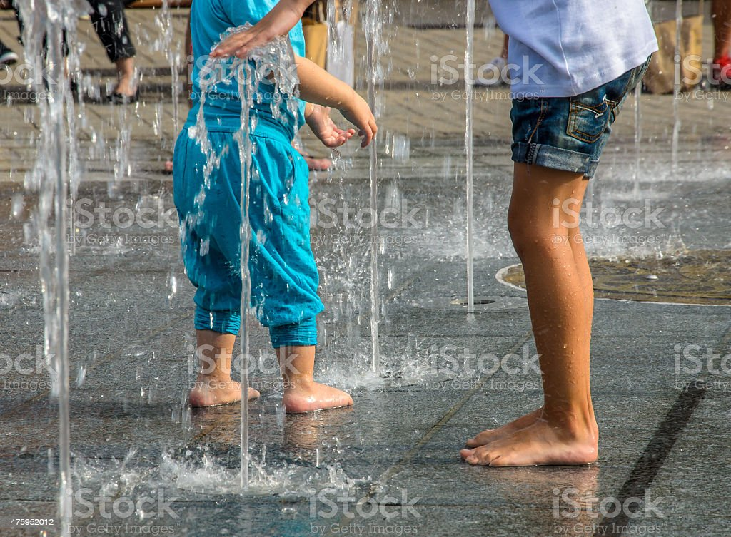 Kids playing in fountainn stock photo