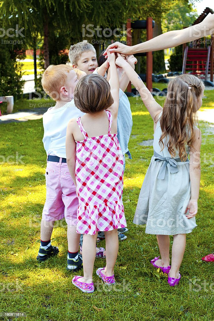 Kids Playing in Garden Five preschool kids playing in the playground. 4-5 Years Stock Photo