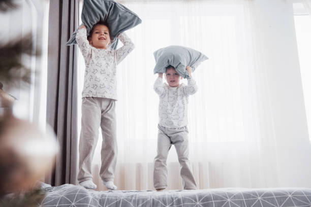 Kinder spielen im Elternbett. Kinder wachen im sonnigen weißen Schlafzimmer auf. Junge und Mädchen spielen in passenden Pyjamas. Schlafbekleidung und Bettwäsche für Kind und Baby. Kindergarten-Interieur für Kleinkind. Familienvormittag – Foto