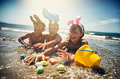 Summer easter on beach. Kids aged 8 and 11 are lying in sea water and having fun wearing easter bunny ears. Kids are catching easter eggs in water.\n