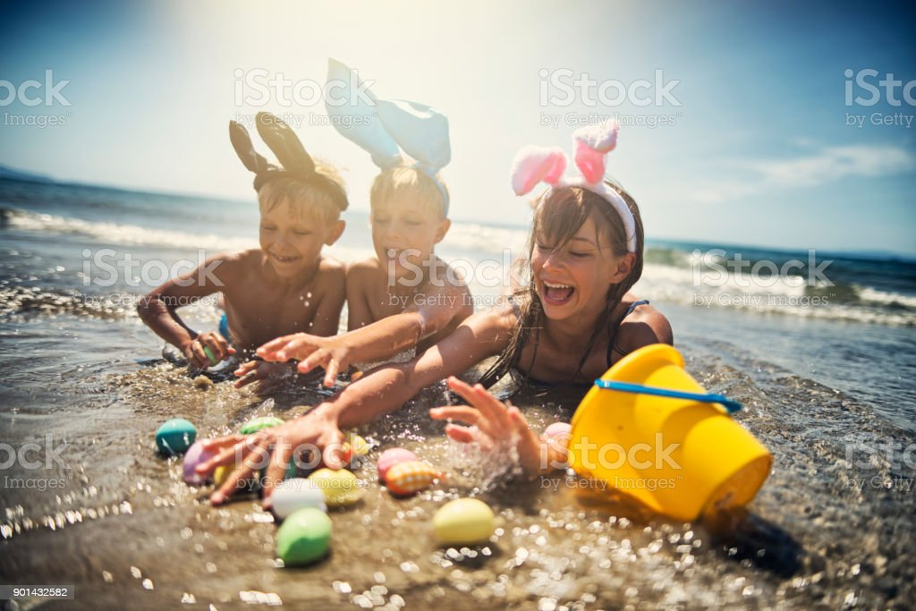Kids playing in sea during summer Easter stock photo