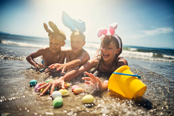kids playing in sea during summer easter - easter foto e immagini stock