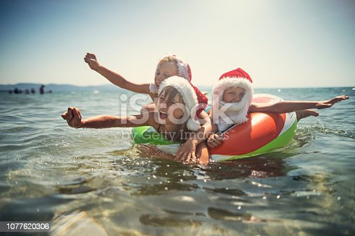 It's summer Christmas at sea. Kids are splashing and having fun on swim ring floating on the sea. Nikon D810
