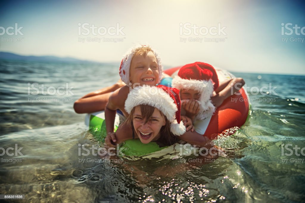 Kids playing in sea on swim ring during summer Christmas stock photo