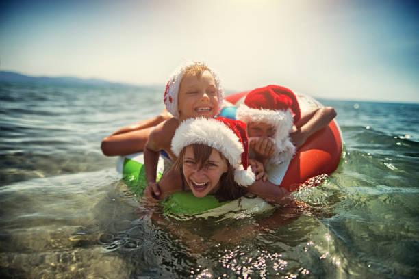 kinder spielen im meer auf schwimmring im sommer weihnachten - weihnachten 7 jährige stock-fotos und bilder
