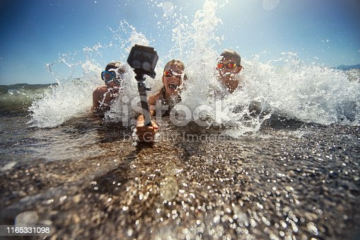 Brothers and sister are having fun in sea. Kids are lying on the front and being splashed by waves. Kids are holding a waterproof action camera on a selfie stick and filming themselves. Nikon D850